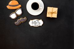 Happy Father Day with hat, glasses, moustache cookies, gift and coffee on black background top view mockup. Happy Father Day celebration with hat, glasses stock photo