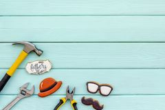 Happy Father Day with moustache, glasses and hat cookies and instruments on mint green wooden background top view mockup. Happy Father Day celebration with royalty free stock image