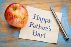 Happy Father Day on napkin. Happy Father`s Day - handwriting on a napkin with apple Stock Image
