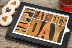 Happy father day. Happy father's day - a word abstract in antique wood letterpress printing blocks on a digital tablet with heart biscuit cookies royalty free stock photos