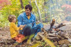 Happy father doing barbecue with his son on an autumn day Stock Photo