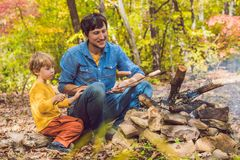 Happy father doing barbecue with his son on an autumn day Royalty Free Stock Images