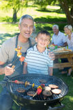 Happy father doing barbecue with his son Stock Image