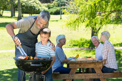 Happy father doing barbecue with his son Stock Images