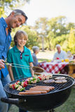 Happy father doing barbecue with his son Stock Photos