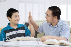 Happy father doing high five with his son. Image of happy father doing high five with his son while studying together in the living room Stock Images