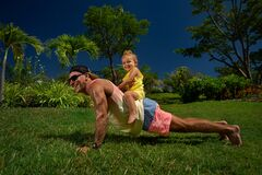 Happy father doing push up exercise with  daughter on back in park