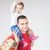 Happy father and funny baby holding bags with purchases Royalty Free Stock Images