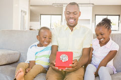 Happy father getting a gift by his son and his daughter. In living room Royalty Free Stock Photos
