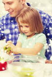 Happy father with girl making dinner at home Stock Image