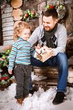 Happy father gives a Christmas gift to his son in decorations with fir tree with gift boxes and wooden background. Christmas happy family of two persons happy royalty free stock photo