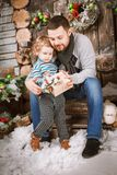 Happy father gives a Christmas gift to his son in decorations with fir tree with gift boxes and wooden background. Christmas happy family of two persons happy stock images