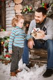 Happy father gives a Christmas gift to his son in decorations with fir tree with gift boxes and wooden background. Christmas happy family of two persons happy stock image
