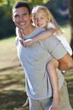 Happy Father Giving Daughter Piggy Back In A Park. A young father with his blond daughter on his shoulders having fun in a sun bathed green park Stock Images
