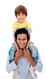 Happy father giving his son piggyback ride. Against a white background Stock Photo
