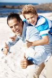 Happy father giving his son piggyback ride Stock Image