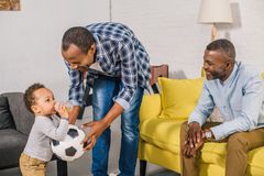 Happy father and grandfather looking at adorable toddler holding soccer ball and drinking from baby bottle. At home stock image