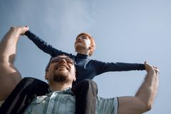 Happy father has a little son on his shoulders. The concept of fatherhood stock images
