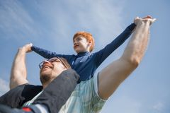 Happy father has a little son on his shoulders. The concept of fatherhood royalty free stock images