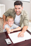 Happy father helping son with his math homework at table Stock Image