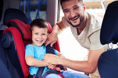 Happy father helps his son to fasten belt on car seat Stock Photos