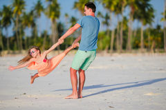 Happy father and his adorable little daughter at tropical beach. Caucasian family having fun together on suumer vacation Royalty Free Stock Images