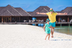 Happy father and his adorable little daughter at tropical beach having fun. Happy father and adorable little daughter at tropical beach having fun Royalty Free Stock Images