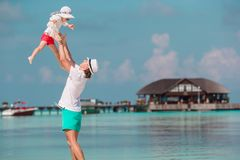 Happy father and his adorable little daughter at tropical beach having fun royalty free stock image