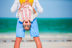 Happy father and his adorable little daughter at tropical beach having fun. Kid hanging upside down in the hands of her Stock Images