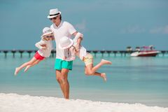 Happy father and his adorable little daughters at tropical beach having fun stock photos