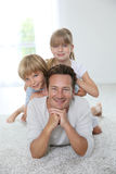 Happy father with his children lying on carpet floor Royalty Free Stock Photos