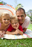 Happy father and his children lying on the grass. In a park looking at the camera with a tent in background Royalty Free Stock Photos