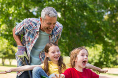 Happy father and his children playing with a wheelbarrow Royalty Free Stock Images