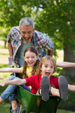 Happy father and his children playing with a wheelbarrow Royalty Free Stock Photography