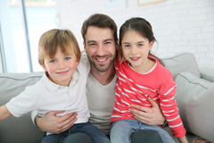 Happy father with his children sitting on the sofa Stock Photos