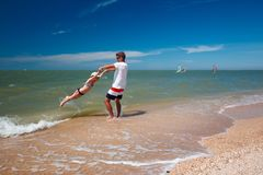 Happy father and his daughter at the beach having fun.  stock photography