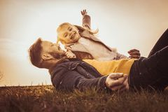Happy father with his daughter outdoor. Happy father playing and lying on grass with his daughter royalty free stock photos