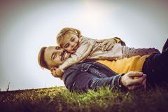 Happy father with his daughter outdoor. Happy father playing and lying on grass with his daughter stock image
