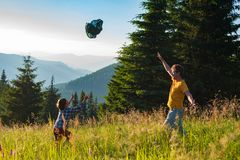 Happy father and his joyful small son are playing on the mountai. N meadow, among a lush green grass, tossing a scarf against a panorama of the mountains royalty free stock photography