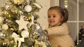 Happy father and his little daughter decorating the Christmas tree at home. royalty free stock image