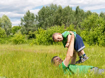 Happy father and his little son. Are playing in the field Stock Photography
