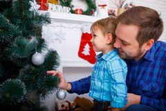 Happy father and his little son decorating the Christmas tree at home. A happy father and his little son in a blue shirt decorate the Christmas tree at home stock photos