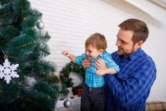 Happy father and his little son decorating the Christmas tree at home. A happy father and his little son in a blue shirt decorate the Christmas tree at home royalty free stock images