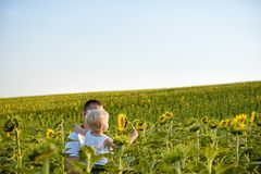 Happy father with his little son in his arms standing on a green field of sunflowers against a blue sky royalty free stock photo