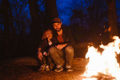 Happy father and his little son sitting together on the logs in front of a fire in a hike in the forest at the night. stock photography