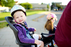 Happy father and his little toddler daughter rinid a bike together Stock Photo