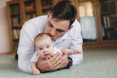 Happy father with his newborn daughter in his house. Stock Images