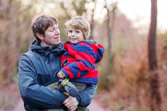 Happy father with his son on arm outdoors. Happy dad holding his son, little funny kid boy on arm, on cold day, walking together in a park in spring, autumn or Royalty Free Stock Image