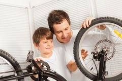 Happy father and his son checking bicycle tires Royalty Free Stock Image