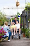 Happy father with his son and daughter playing with a wheelbarrow in the greenhouse. Shot of happy father with his son and daughter playing with a wheelbarrow stock photos